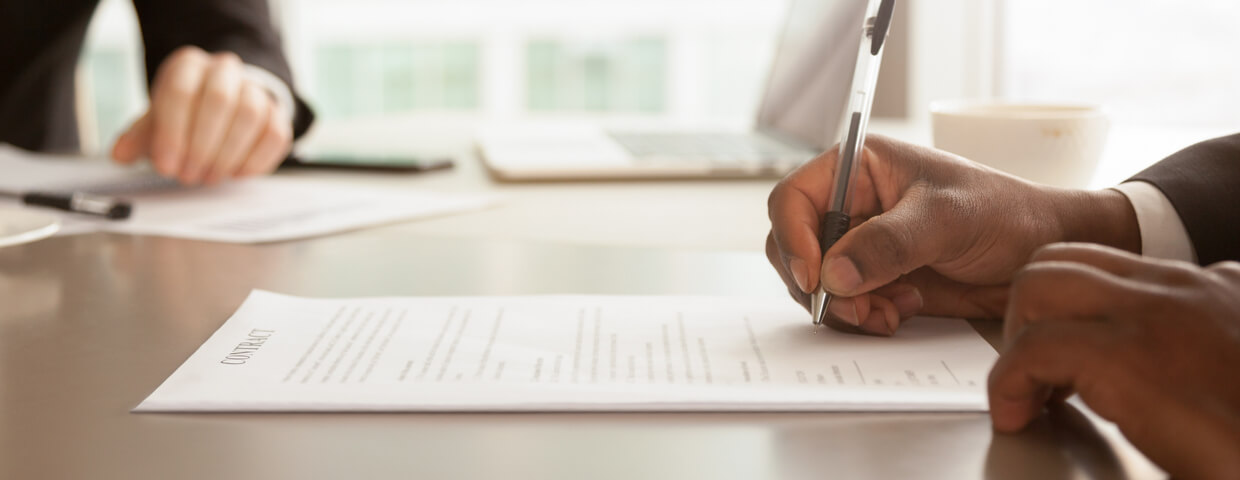 Horizontal close up photo african businessman sitting at desk holds pen signing contract paper, lease mortgage, lease agreement concept